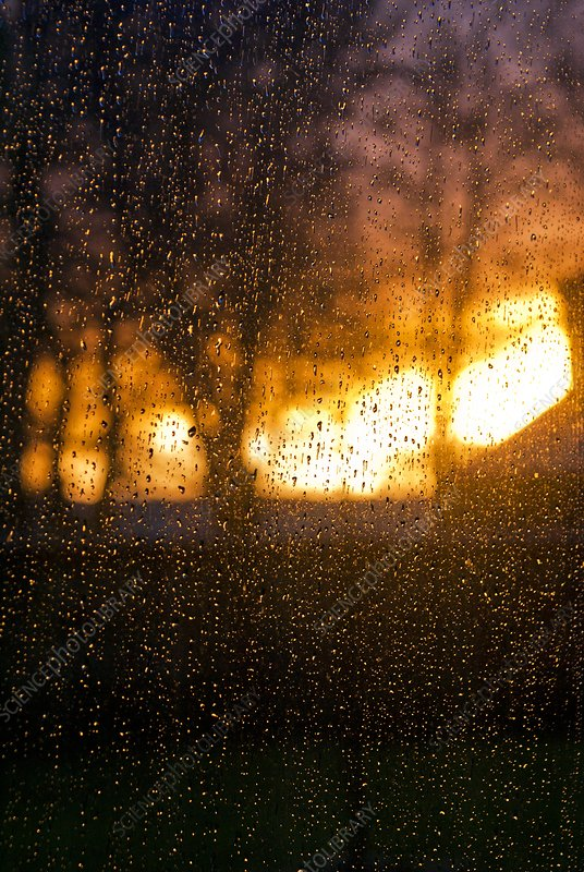 Rain drops on a window at sunrise