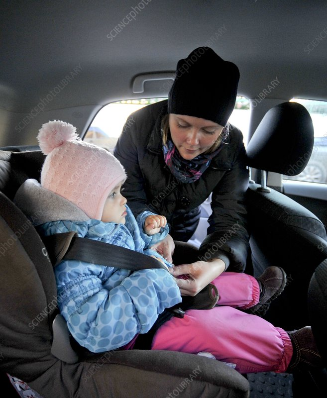 Woman putting child in car seat