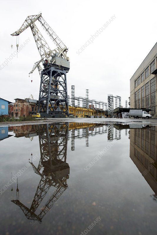 Crane in dock reflected in water