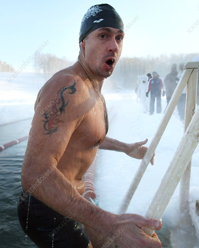 Swimmer climbing out of icy water