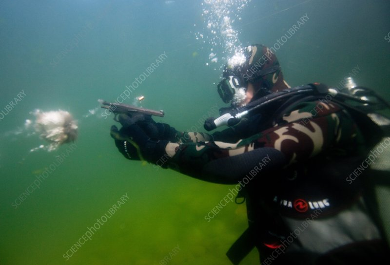 Diver firing a pistol underwater