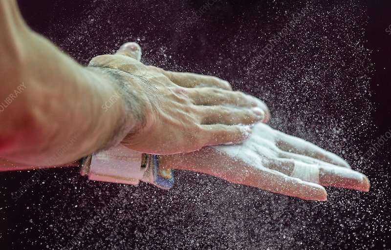 Gymnast applying rosin to hands