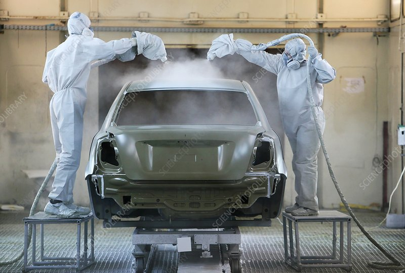Workers painting a car body shell