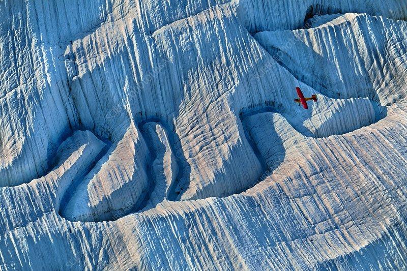 Bush plane over glacier, aerial view, USA