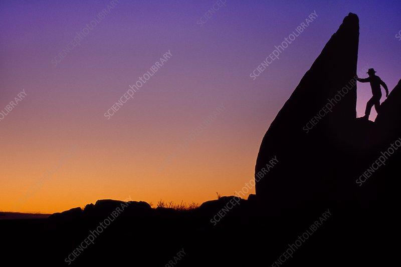 Rock climber at sunset, Australia