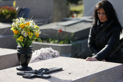 Woman praying at a grave in a cemetery