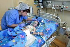 Nurse with child heart surgery patient
