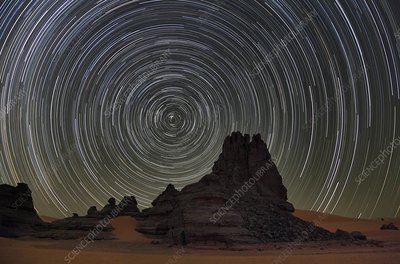 Star trails over Saharan rock formations