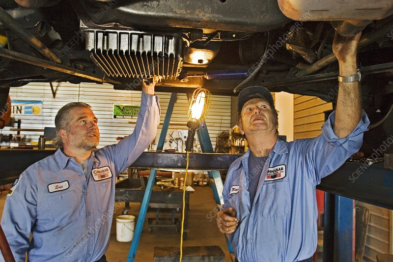 Mechanics repairing recreational vehicle