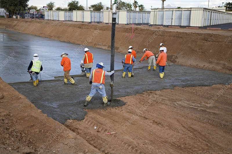 Workers lining a canal with concrete