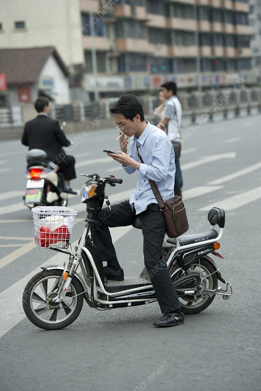 Man on a battery-powered moped smoking