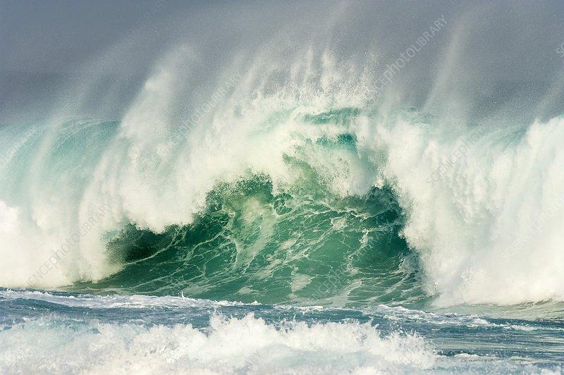Huge wave crashing against the shoreline