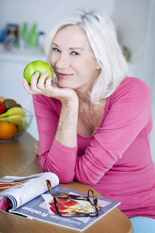 Elderly person eating fruit