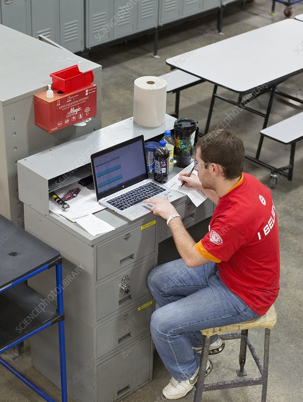 Worker using laptop in a factory