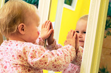 Toddler interacting with a mirror