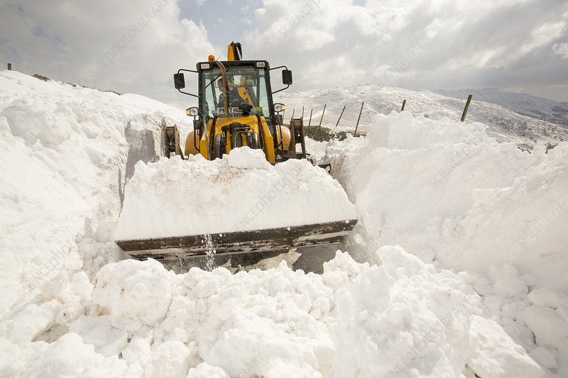 Digger clearing snow drifts