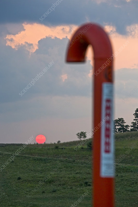 Natural gas pipeline marker at sunset