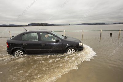 A motorist travels through flood waters