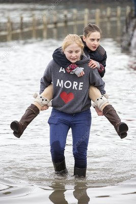 Children wade through flood waters