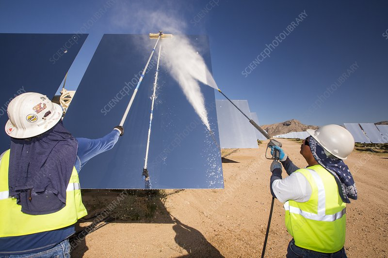 Workers washing the heliostats