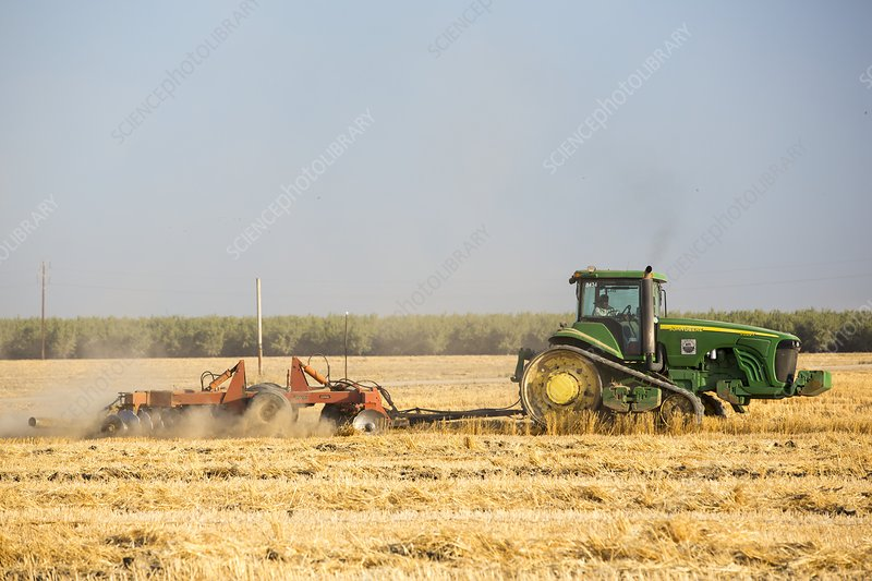 A farmer ploughs a field in Wasco
