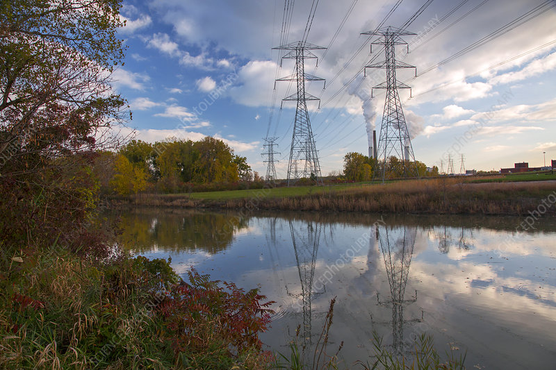 Electricity pylons by a lake