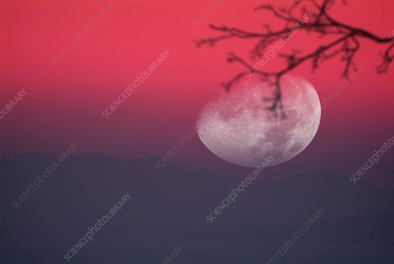 Moon setting behind mountains