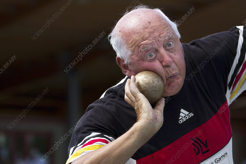 Older man about to throw shot put