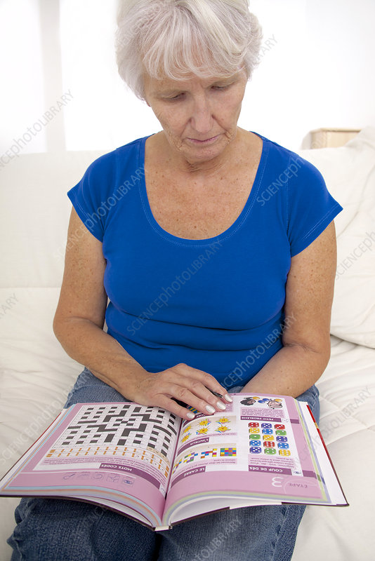 Older lady reading puzzle book