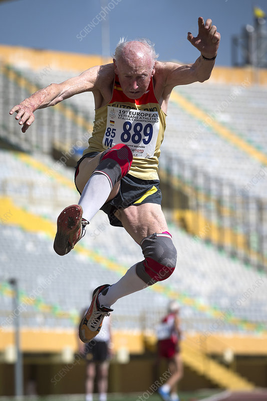 Elderly male athlete jumping mid-air