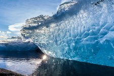 Blue iceberg on sandy beach