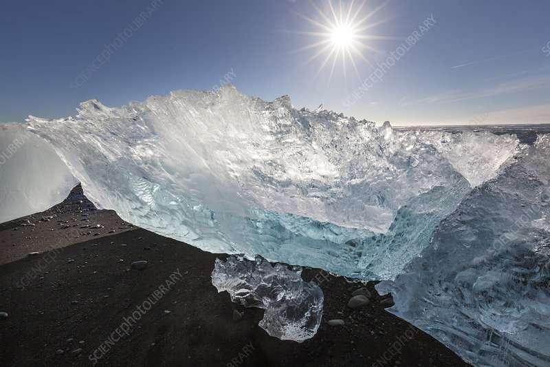Blue icebergs on sandy beach