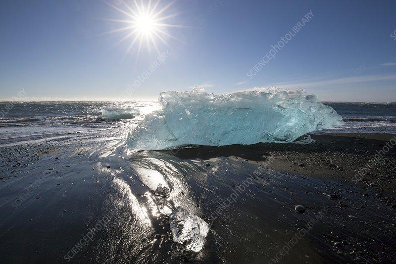 Blue iceberg on sandy beach