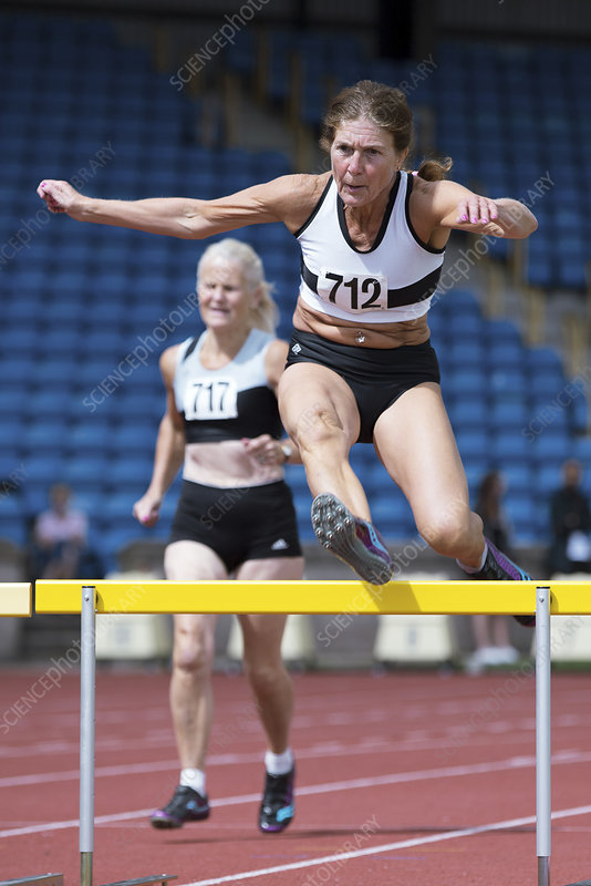 Senior female athlete clears hurdle