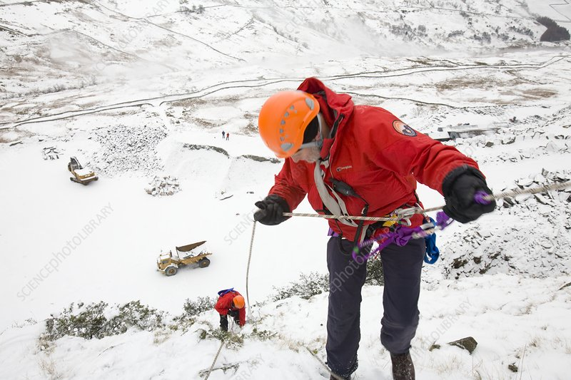 Mountain rescue team member abseiling