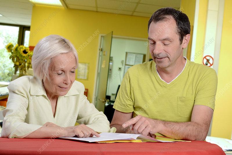 Hospital nurse assisting elderly woman