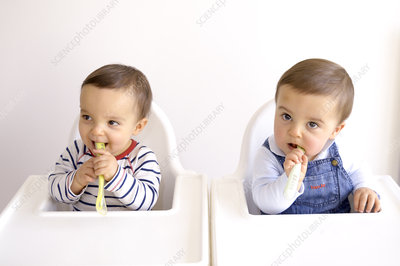 Twin baby boys playing with spoons