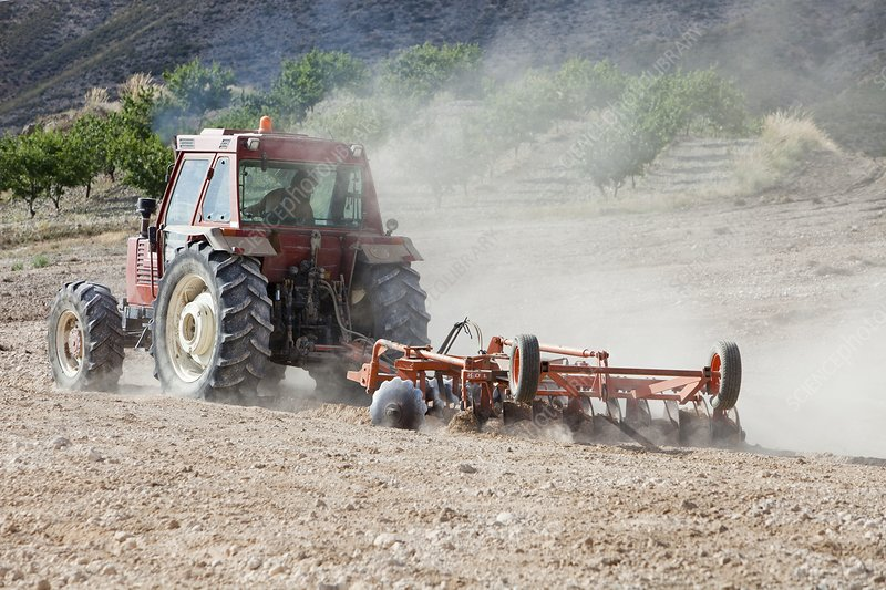 A farmer tilling dry dusty soil