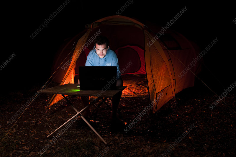 Man using laptop outside a tent