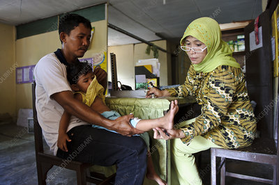 Doctor examining a boy, Indonesia