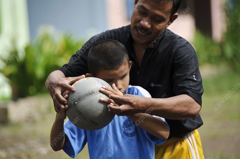 Blind boy with football, Indonesia