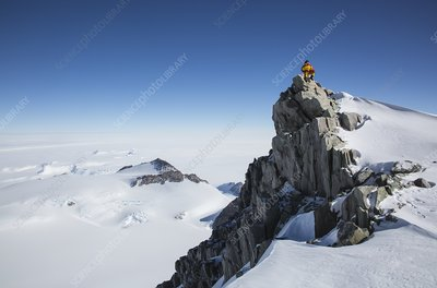 A climber on a rocky peak in Antarctica