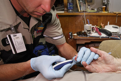 Paramedic Checking Blood Glucose Levels