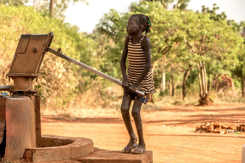 Young girl pumping water