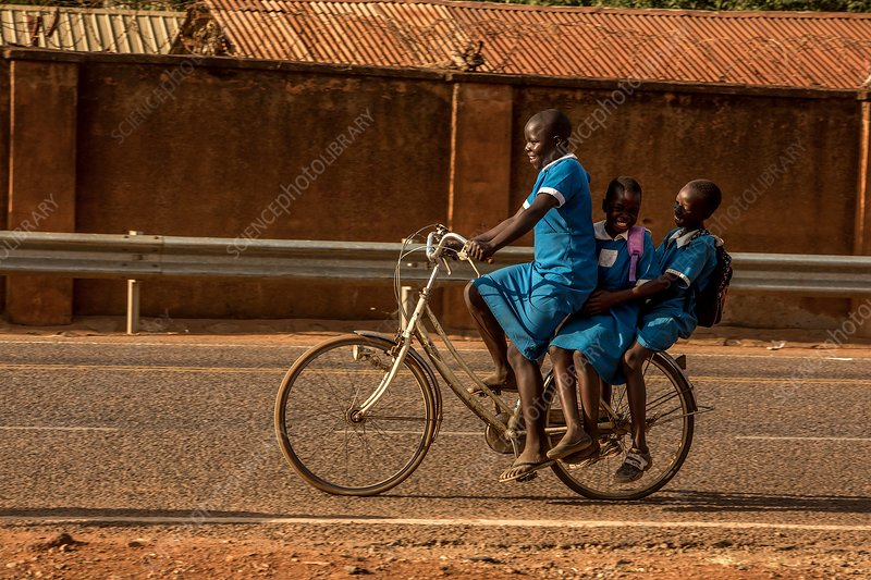 Schoolchildren riding a bicycle