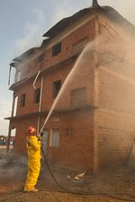 Firefighter using a hose on a burning building