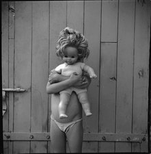 Child hiding behind a doll