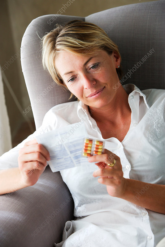 Woman reading the instructions of medication