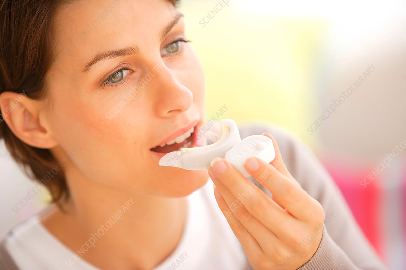 Woman bleaching teeth