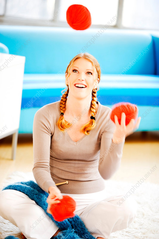 Woman juggling with balls of wool